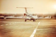 私人喷气式飞机飞机停车处在机场 在橙色日落的私有飞机 库存图片