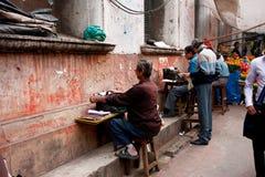 私有工作者在室外老的打字机打印文件在印度 库存照片