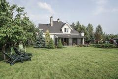 私有房子和它的庭院在美丽的天空下 免版税库存照片