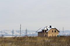 私有现代二层楼的房子建设中没有在一个领域的篱芭在冬天 免版税库存照片