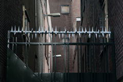私有财产,篱芭区域 有有刺的保护的黑金属门 年迈的纸织地不很细背景,减速火箭的颜色 图库摄影