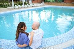 秃头坐赤足近的游泳池的丈夫和妻子 免版税库存照片