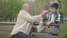 秃头成熟人在公园坐与书的长凳,谈话与他的孙子 然后人们握手和 股票视频