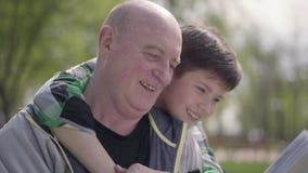 秃头成熟人在公园坐读书,小男孩的长凳拥抱他从后面 ?? 股票视频