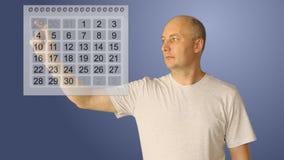 年轻秃头人与真正日历一起使用 男性选择两日期在起动和结尾期内 休息的飞行的perioad或 免版税库存图片
