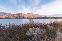 秋叶和草与湖和峭壁由日落光显著点燃了在背景中 库存图片