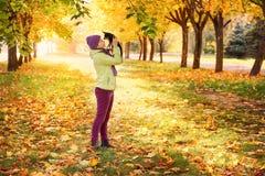 秋叶的女婴在新鲜空气的公园 使用与一条小狗的女孩户外在秋天 免版税库存照片