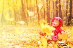 秋叶的愉快的逗人喜爱的小女孩 免版税库存图片