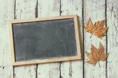 秋叶的顶视图图象在黑板旁边的在木织地不很细背景 复制空间 退色的减速火箭的被过滤的图象 免版税库存图片