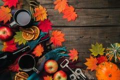 秋叶,两个杯子酒,与格子花呢披肩的红色苹果在老葡萄酒木背景 免版税图库摄影