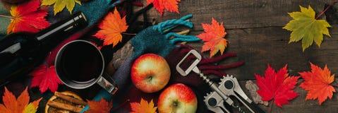 秋叶,两个杯子酒,与格子花呢披肩的红色苹果在老葡萄酒木背景 库存图片