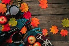 秋叶,两个杯子酒,与格子花呢披肩的红色苹果在老葡萄酒木背景 图库摄影