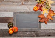 秋叶,在木背景的南瓜与在黑板的拷贝空间 图库摄影