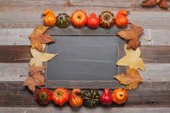 秋叶,在木背景的南瓜与在黑板的拷贝空间 免版税库存照片