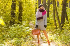 秋天、季节和人概念-外套的妇女有站立在秋天公园的棕色袋子的 免版税库存图片