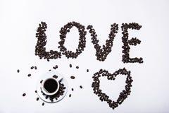 秋天、槭树秋天叶子与一杯热的咖啡的和咖啡豆的题字在木桌背景爱  免版税库存图片