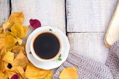 秋天、秋天叶子、热的通入蒸汽的咖啡和在木桌背景的一条温暖的围巾 免版税库存照片