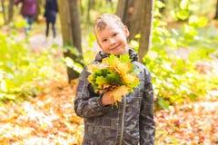 秋天、自然和人概念-英俊的男孩青少年的举行的花束秋叶和微笑 免版税图库摄影