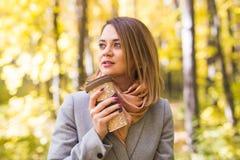秋天、饮料和人概念-年轻美丽的妇女接近的画象灰色外套的用咖啡 免版税库存照片