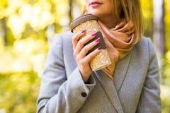 秋天、饮料和咖啡概念-接近灰色外套的妇女有咖啡的 免版税库存照片