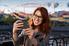 秋天一个美丽的女孩的selfie画象玻璃的 库存照片