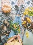 秋天与女性和猫的茶时间在铺磁砖的地板上 免版税库存图片