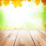 秋天与槭树叶子和木桌的自然背景 免版税库存照片