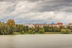 秋天与池塘和公园的城市风景 免版税库存照片