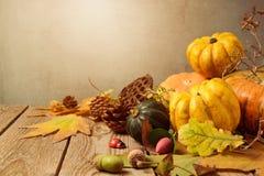 秋天与秋天叶子和南瓜的季节背景在木桌上 免版税库存图片