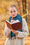秋天与美丽的妇女阅读书的放松概念 库存照片