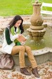 秋天书喷泉公园读了妇女年轻人 免版税库存照片