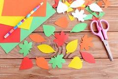 秋天五颜六色的叶子从纸,铅笔,剪刀,在木背景的色纸板料切开了 教剪切口 免版税库存照片