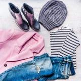 秋天冬天女性衣物集合拼贴画  桃红色外套,蓝色被剥去的牛仔裤, sriped女衬衫、被编织的帽子和黑皮靴ove 库存照片