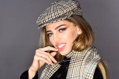 秋天冬天行家样式 辅助部件帽子和一条时髦的方格的围巾的时兴的女孩 库存照片