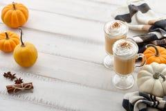 秋天南瓜与打好的奶油的香料拿铁在白色木背景 免版税库存照片
