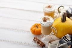 秋天南瓜与打好的奶油的香料拿铁在白色木背景 库存图片