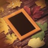秋天叶子和框架的照片在桌上 免版税图库摄影