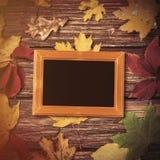 秋天叶子和框架的照片在桌上 免版税库存图片