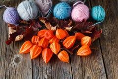 秋天叶子和羊毛在土气木背景滚成线球 免版税库存照片