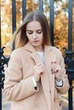 秋天叶子的美丽的女孩通过在一个晴朗的下午的城市街道走在外套和一件温暖的夹克 免版税库存图片