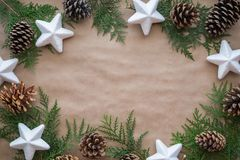 秋天和冬天圣诞节假日贺卡的平的位置构成 杉木锥体、白色星和金钟柏分支在kr 免版税库存照片