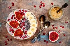 秋天和冬天早餐集合 Acai superfoods圆滑的人滚保龄球与chia种子,石榴,香蕉,新鲜的无花果,榛子黄油 免版税图库摄影