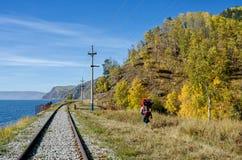 秋天在南贝加尔湖的Circum贝加尔湖铁路有背包徒步旅行者的 免版税图库摄影