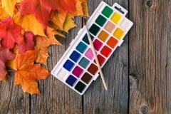 秋天在土气桌上的槭树叶子 免版税库存照片