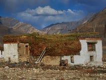 秋天在山村:白色房子在黄色谷中站立,在屋顶谎言大干草堆,在那里墙壁附近是 库存图片