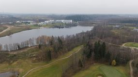 秋天在湖岸立陶宛空中寄生虫顶视图的高尔夫球领域 免版税库存照片