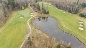 秋天在湖岸立陶宛空中寄生虫顶视图4K UHD录影的高尔夫球领域 免版税库存照片