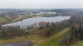 秋天在湖岸立陶宛空中寄生虫顶视图4K UHD录影的高尔夫球领域 免版税库存图片