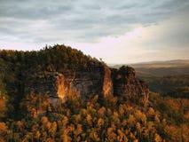 秋天在砂岩的日落视图晃动对漂泊瑞士的秋天五颜六色的谷 砂岩峰顶在森林里 库存图片