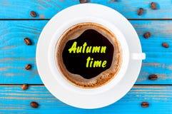 秋天在顶视图早晨咖啡杯的时间题字在蓝色木背景 免版税图库摄影